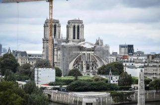 This photograph taken on August 19, 2021 in Paris, shows a giant crane outside Notre-Dame Cathedral, which was partially destroyed when fire broke out beneath the roof on April 15, 2019. (Photo by STEPHANE DE SAKUTIN / AFP)
